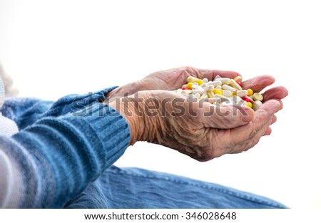 Cropped view of senior woman holding handful of pills over white - stock photo