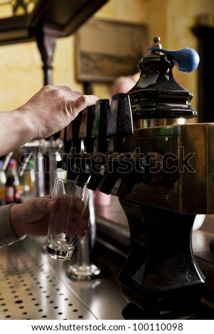 Cropped view of the hands of a barman dispensing drought beer from generator - stock photo