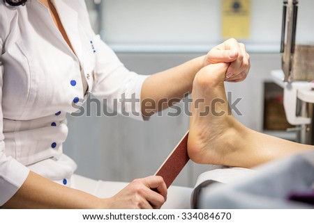 Cropped view of woman getting a pedicure  - stock photo