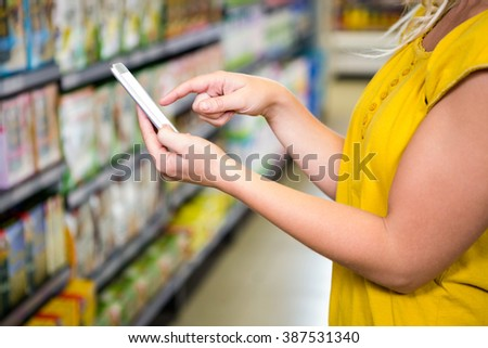 Cropped view of woman using her smartphone in supermarket - stock photo