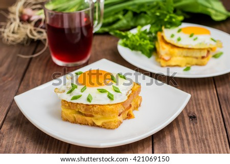 Croque-Madame, a French sandwich with greens and berry juice for breakfast. Wooden table. - stock photo
