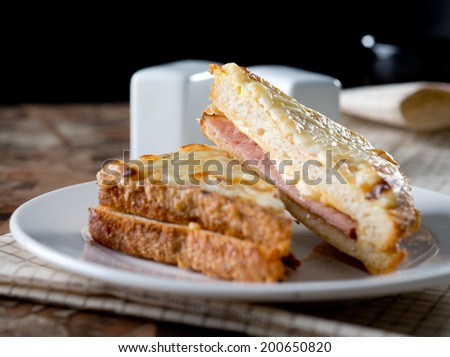 Croque Monsieur - most known French toast with Ham and Cheese served on white plate front view - stock photo