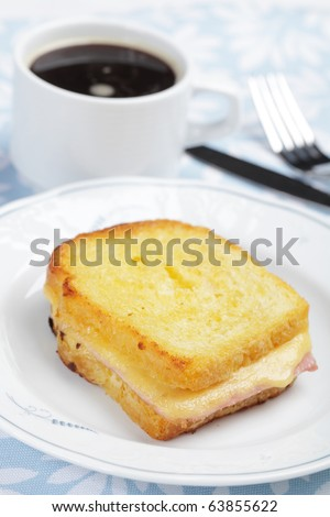 Croque-monsieur sandwich and a cup of black coffee