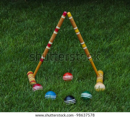 Croquet mallets and balls on grass background - stock photo