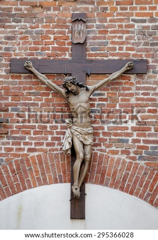 Cross against a brick wall - stock photo