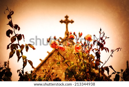 Cross and roses. A church in Dinan (Brittany, France). Selective focus on the flowers. Retro aged photo with scratches.  - stock photo