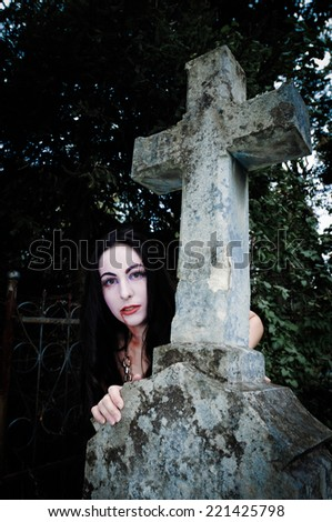Cross and vimpire girl on cemetery - stock photo