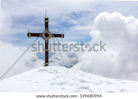 Cross at snowy peak in the mountains - stock photo