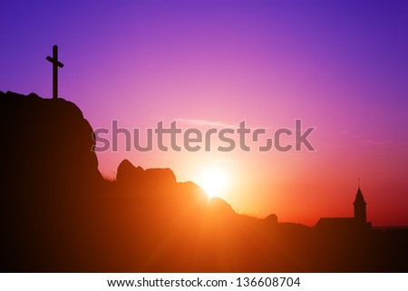 Cross, Church and Sunrise, Sunset - Single cross and church on a rocky hilltop. - stock photo