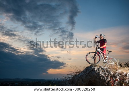Cross country biker drinking water on top of a mountain with bike in the evening, sky background. side view - stock photo