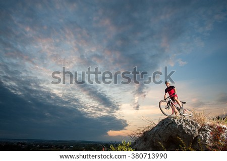 cross country biker relaxing on the top of the mountain, enjoying beautiful sunset on overview point. - stock photo