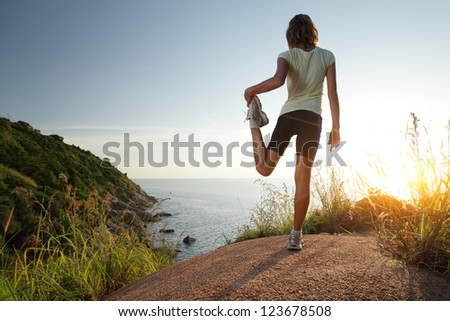 Cross country racer stretching on top of a hill and enjoying sunset sea view - stock photo