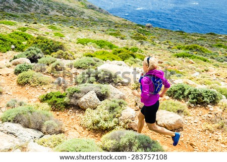 Cross country running woman trail running in inspirational mountains on summer beautiful day. Training and working out runner jogging fitness and exercising in nature, rocky footpath on Crete, Greece - stock photo