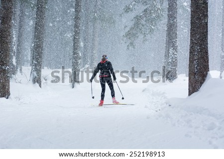 Cross country skier tackling bad weather conditions.