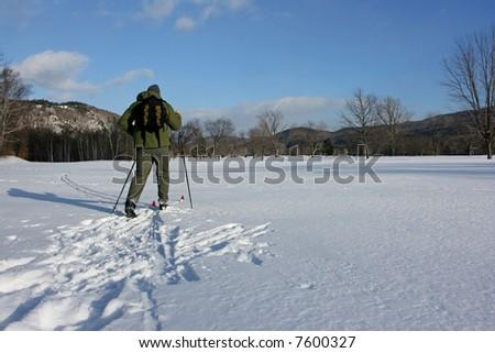 Cross country skiier skiing across the winter snow. - stock photo
