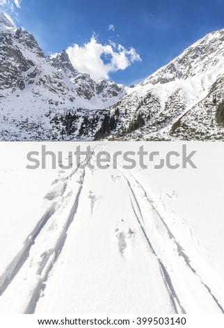 Cross-country skis traces on snow on frozen Lake Morskie Oko, Polish Tatra Mountains. - stock photo