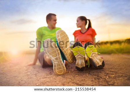 Cross-country trail running couple stretching and exercising at sunset - stock photo