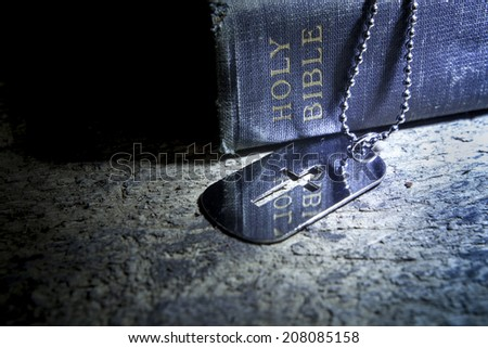 Cross dog tag necklace and The Bible - stock photo