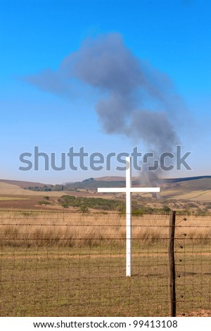 cross in front of a fence with a fire - stock photo