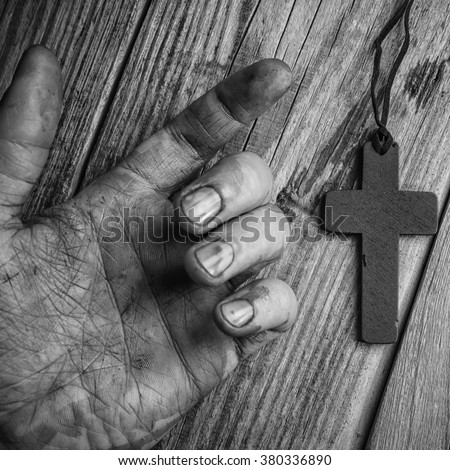 Cross in hand on wooden background - stock photo