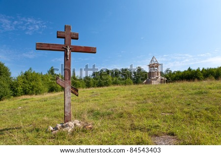 Cross in honor of the basis of church and under construction orthodox church on a hill - stock photo