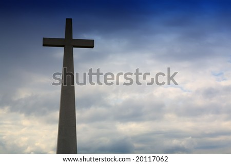 Cross in silhouette and the clouds in the sky