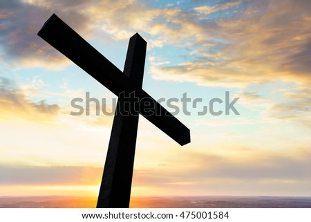 Cross in silhouette with a colorful sky and cloud