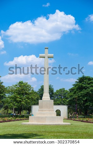 cross in the cemetery Behind the sky is overcast. Cemetery with grass and trees. - stock photo