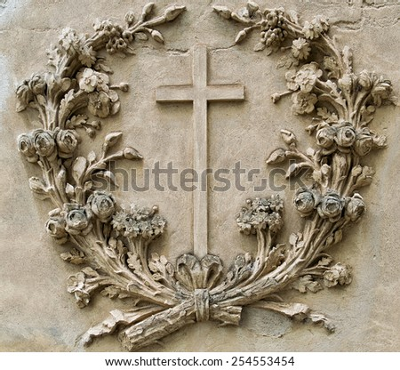 cross in the center of a garland of flowers made on an ancient wall - stock photo
