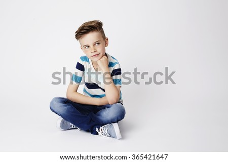 Cross legged kid sitting in white studio