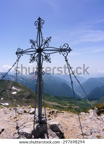 Cross located on the summit of the mountain in the Italian Alps. - stock photo