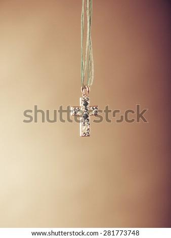Cross necklace pendant. Christian religion faith symbol. Christianity. Instagram filtered. - stock photo
