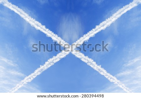Cross of Aircraft Condensation Trails or Contrails of the Plane in the Blue Sky - stock photo