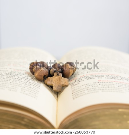 Cross of rosary beads resting against open bible - stock photo