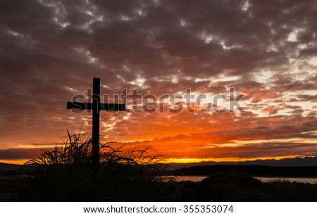 Cross on a hill as the morning sun comes up for the day - stock photo