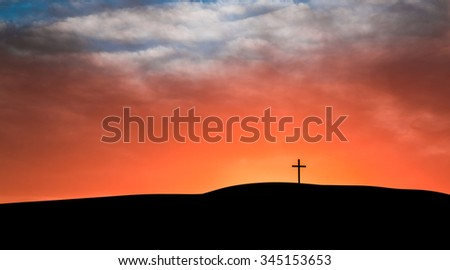 Cross on a hill with the sun setting behind the hill lighting up the clouds.