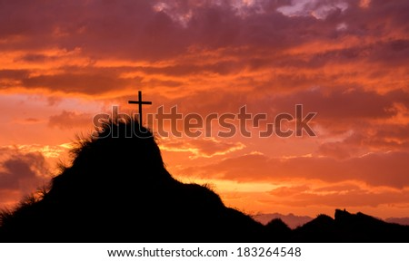 Cross on a tall hill with the sky behind it lit up as the sun goes down.