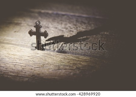 cross on the brown wooden table background - stock photo