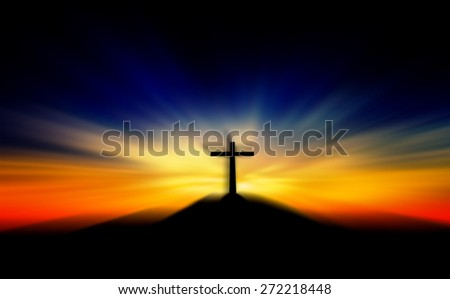 Cross on the hill behind the blur sunset. - stock photo