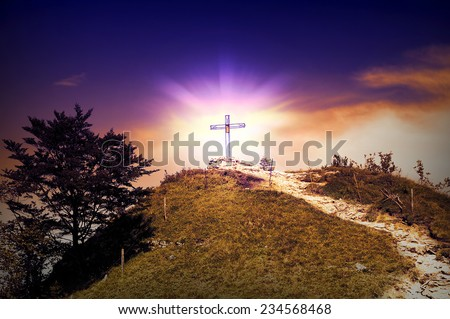 Cross on the summit of a mountain - path to belief  - stock photo