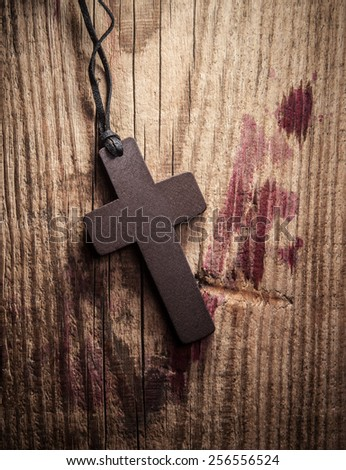 Cross on wooden background with stains of blood - stock photo