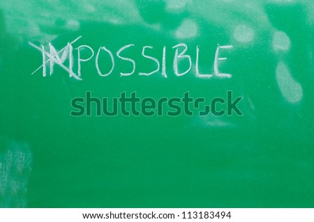 "Cross out letters ""IM"" in the word ""IMPOSSIBLE"" on the green school board - stock photo"