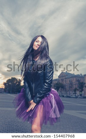 cross processed colors image sexy brunette outdoors weared black leather jacket and ballet tutu-skirt violet color - stock photo