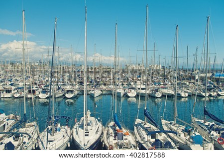 cross-processed image of marina with white sailboats and yachts on sunny day in Barcelona, Spain - stock photo