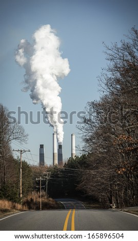 Cross processed image of paved road leading to industrial smoke stacks billowing out pollution. - stock photo