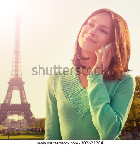 cross processed picture. France with Eiffel Tower in background. Cute beautiful Caucasian female model holding a phone in her hand and sliling.  - stock photo