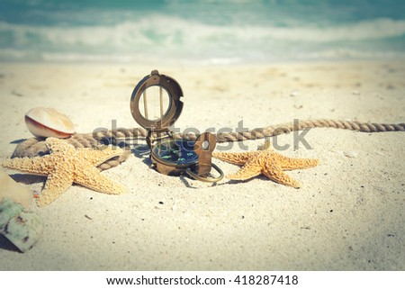 Cross-processed, selective focus compass with shells and rope on an ocean beach