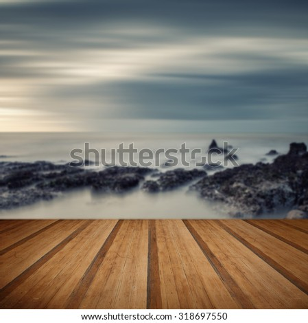 Cross processed vintage style long exposure sea landscape with wooden planks floor - stock photo