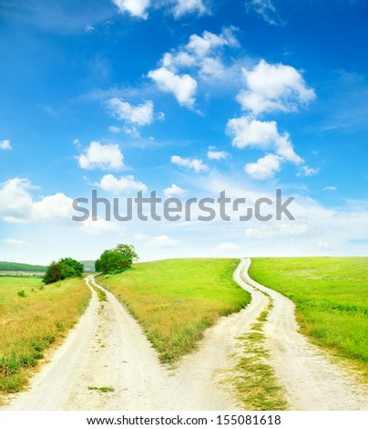 Cross roads horizon with grass and blue sky  - stock photo