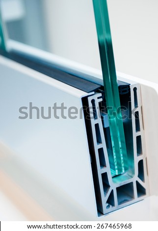 Cross section of a PVC window profile, beside a pvc window frame, over a plastic surface - thermal insulation and environment protection concept - stock photo